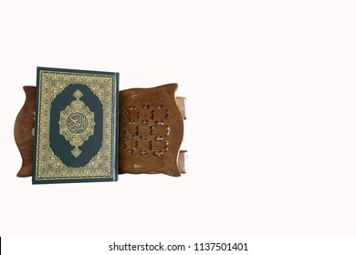 Quran - holy book of Muslims around the world, placed on a wooden board with a white background.