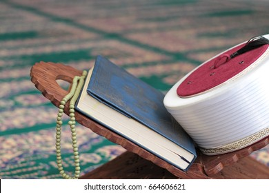 Quran, imam fez and rosary beads on a wooden stand in mosque. Quran is holy book religion of Islam