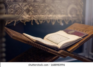 Quran islamic holy book on dark background with with blurred traditional carpet for reading in ramadan night, muslim style and ramadan concept