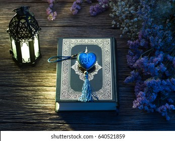 "Quran or Kuran, the islamic holy book, in dark wooden background, with the rosary with the name of God ""Allah"" in arabic text"