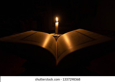 Quran in the mosque at night and light from the candle