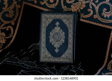 Qur'an in the mosque - open for the black background prayer of Muslims around the world, placed on a wooden board of the Qur'an.
