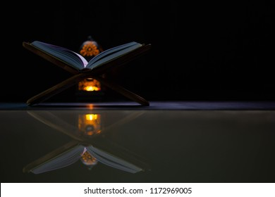 Quran in the mosque - open for prayers The black background of the Muslims around the world placed on a wooden board Quran in the mosque - open for prayers Black background