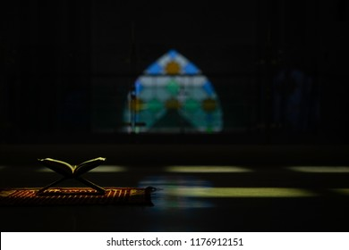 Quran in the mosque - open for prayers The black background of the Muslims around the world placed on a wooden board Quran in the mosque - open for prayers Black background , low light