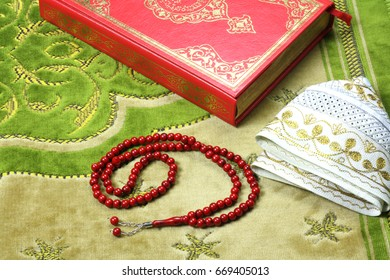 Quran, muslim hat and rosary beads on a prayer rug. Quran is holy book religion of Islam