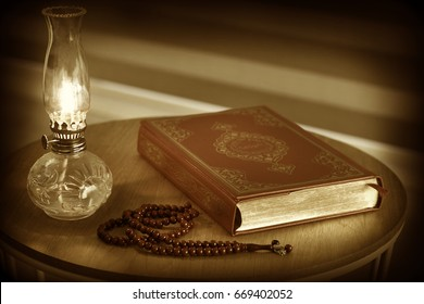 Quran, rosary beads and oil lamp. . Quran is holy book religion of Islam. Sepia style image.
