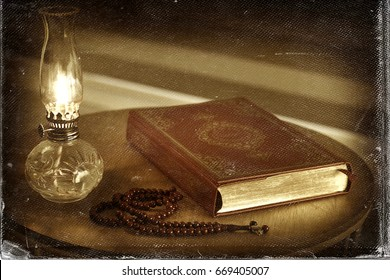 Quran, rosary beads and oil lamp on a wooden stand. Old, worn picture look image. Quran is holy book religion of Islam.
