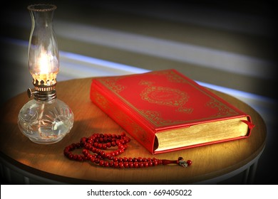 Quran, rosary beads and oil lamp on a wooden stand. Quran is holy book religion of Islam.