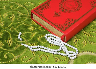 Quran and rosary beads on a prayer rug. Quran is holy book religion of Islam