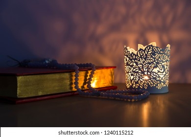 Quran and rosary beads on the wooden background with light lantern or candle for Islamic concept. Holy book Koran for Muslims holiday, Ramadan,blessed Friday message and three months