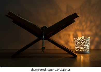 Quran and rosary beads on the wooden lectern with light lantern or candle for Islamic concept. Holy book Koran for Muslims holiday, Ramadan,blessed Friday message and three months