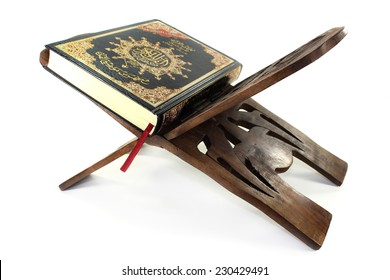 Quran with Quran wooden stand in front of white background