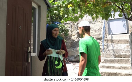 The Qurban meat to be distributed to the neediest or those suffering adversity and poverty. Muslim man gives sacrificial sheep meat to poor woman. Zakat is a form of alms-giving
