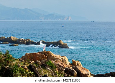 QUY NHON, VIETNAM - FEB. 20, 2018: An unidentified man collecting nylon bags on the rocks as a way of earning his living.