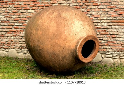Qvevri – jug for wine-making on brick wall background. Like an amphora.