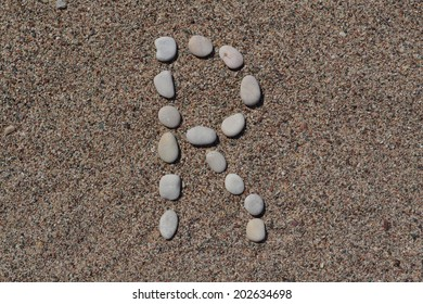 R letter made of stones on sand