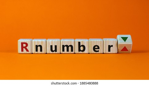 R - reproduction number up or down symbol. Wooden cubes with word R - reproduction number on beautiful orange background. Covid-19 pandemic R - reproduction number concept.