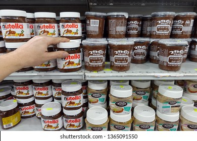 RA'ANANA, ISRAEL - MARCH 3, 2019: 'Shelves with Nutella and Hashachar Ha'ole brand chocolate spread. Sweetened hazelnut chocolate spreads from different brands in a Victory Supermarket.