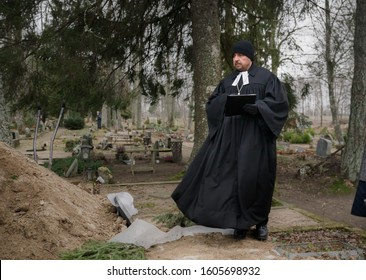 Raasiku / Estonia - January 02 2020: Funeral ceremony in small Lutheran church next to Christmas tree. Priest  standing next to the grave and holding a liturgy honoring a dead person, Cold winter day.