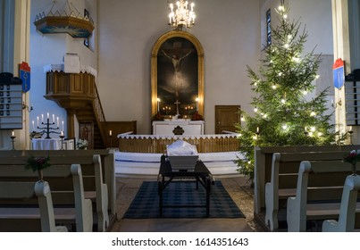 Raasiku / Estonia - January 03 2020: White coffin of the mother waiting for mourning family and friends in Lutheran church. Christmas decorations. Typical funeral tradition.