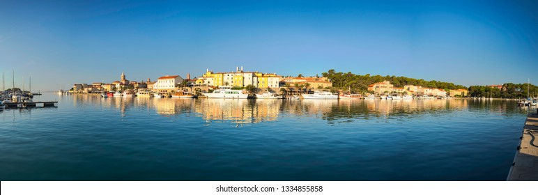 Rab, Croatia - August 26, 2017: Panoramic view of marina in the city of Rab with the city center in the background and bell towers on island Rab in Croatia.