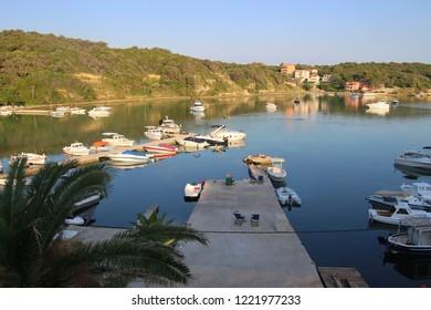 Rab island, Croatia: The bay of Supetarska Draga in early morning light. Boats and jetty. South-east Europe.