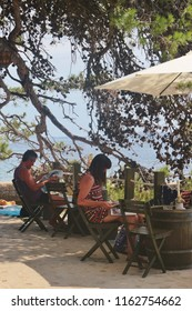 Rab, Rab island, Croatia - July 15, 2018: People relax on a cafe terrace, on the seaside promenade of Rab city. South-east Europe.