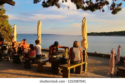 Rab, Rab island, Croatia - July 17, 2018: People relax on a cafe terrace, on the seaside promenade of Rab city. South-east Europe.