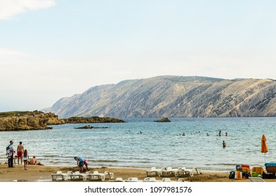 Rab Island, Primorje-Gorski Kotar / Croatia - 28 08 2014: View on a beach on a rab island with few tourists, Adriatic sea and mountains in distance