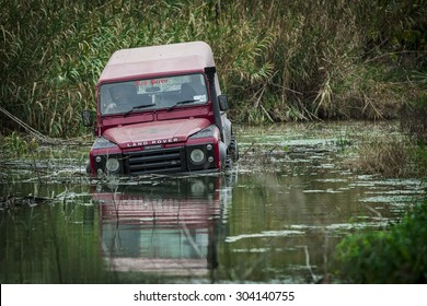 RABAT, MALTA - JANUARY 19, 2014: A 1989 Land Rover Defender wades through deep rain water.  The Defender is one of the most off-road capable vehicles in history.