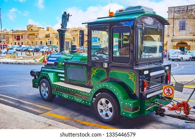 RABAT, MALTA - JUNE 16, 2018: The old-style fun train waits the tourists in Museum square of Rabat with monument of St Joseph and historical housing on the background, on June 16 in Rabat.