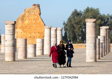 Rabat, Morocco - 29 November 2018: Women walk near Hassan Tower or Tour Hassan which is the minaret of an incomplete mosque in Rabat, Morocco. Remnants of wall at Hassan Tower, Rabat, Morocco