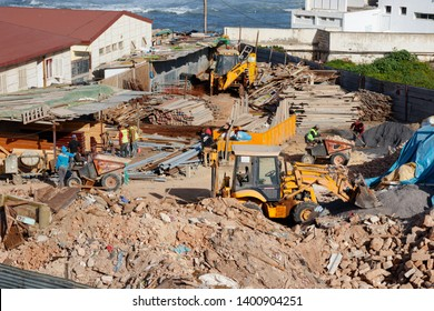 RABAT, MOROCCO - FEBRUARY 22, 2019: Construction yard at the coast of Rabat with workers using backhoe loaders and dumpers to diplace piles of rubble on a sunny afternoon.