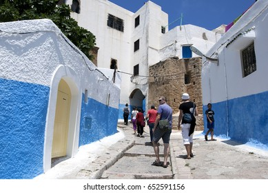 RABAT, MOROCCO - JULY 22, 2013 : Tourists walk through the beautiful streets of Kasbah des Oudaias in the city of Rabat, Morocco. This section of Rabat is famous for its blue and white washed walls.