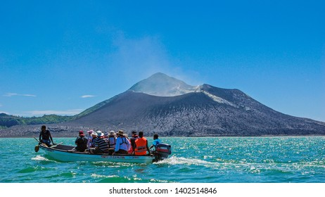 Rabaul, New Britain, Papua New Guinea - October 22 2010: A local boat shuttles tourists over to hike around the moonscape-like base of Mt. Tavurvur. The volcano has erupted on & off since 1994