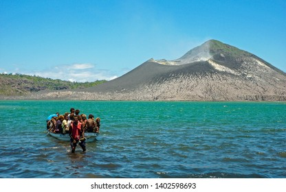 Rabaul, New Britain, Papua New Guinea - October 22 2010: A boat full of local people, in Matupit Bay. Tavurvur volcano smokes gently in the background