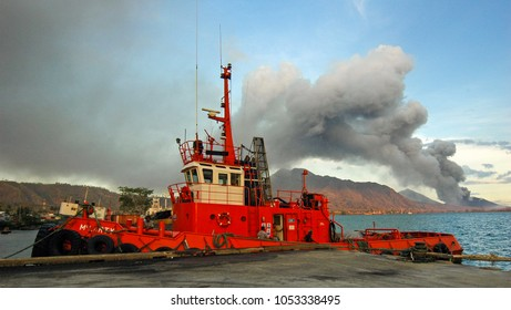 Rabaul / Papua New Guinea - April 7 2009: Tugboat lies at the dock in front of the plume from Mt. Tavurvur. Most of Rabaul is destroyed, and the natural harbour is all that keeps people here.