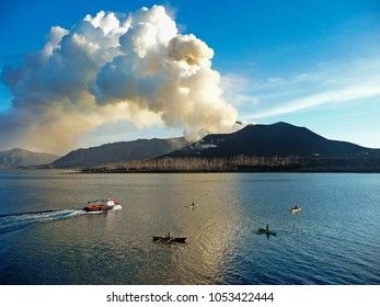 Rabaul / Papua New Guinea - April 7 2009: As Mt. Tavurvur belches smoke and ash, the pilot boat comes out to guide a ship into Simpson Harbor. Local fisherman use hand-lines from their canoes