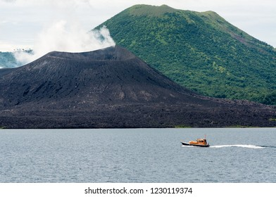 The Rabaul pilot boat passes the smoking crater of Tavurvur, as it returns to base after putting a harbor pilot on an arriving ship.