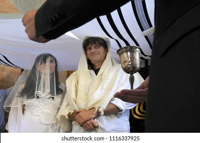 Rabbi blessing Jewish bride and a bridegroom on their wedding day.