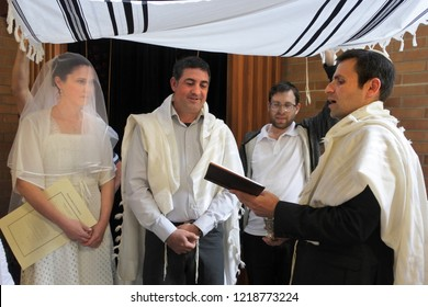 Rabbi blessing Jewish bride and a bridegroom in modern Orthodox Jewish wedding ceremony in synagog.