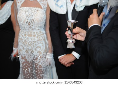 rabbi hold glass of wine at jewish wedding