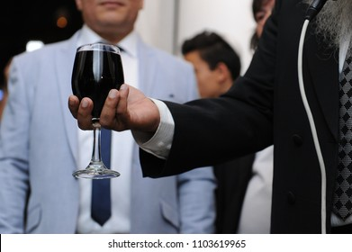 rabbi holds glass of wine at wedding