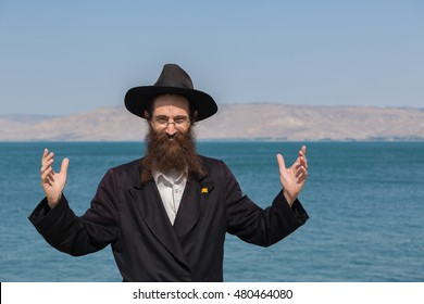 "Rabbi - A man dressed in black looking forward and lift arms up on the ""Kineret"" lake background"