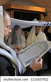Rabbi reads the Ketubah (Jewish prenuptial agreement) of a Jewish bride and a bridegroom in Synagogue on their wedding day.