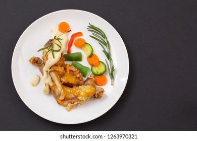 Rabbit legs baked in white wine with bechamel sauce on a ceramic plate with vegetables and rosemary on black background. Dietary rabbit meat cooked in oven. Top view with copy space.