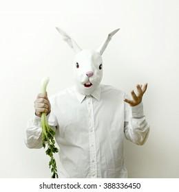 Rabbit masked man eats celery