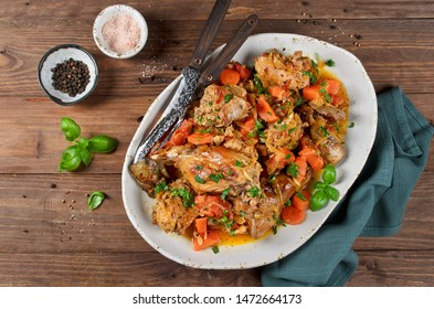 Rabbit stew with onions, carrots and tomatoes. Meat with vegetables stewed in white wine sauce