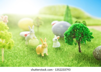 Rabbit toys with easter eggs on a meadow grass. Yellow easter egg spring meadow with a two rabbit and easter eggs. Fairy tale