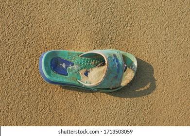 Rab/Croatia-March 31.2007: A children's Diadora slipper shoe left on a sandy beach